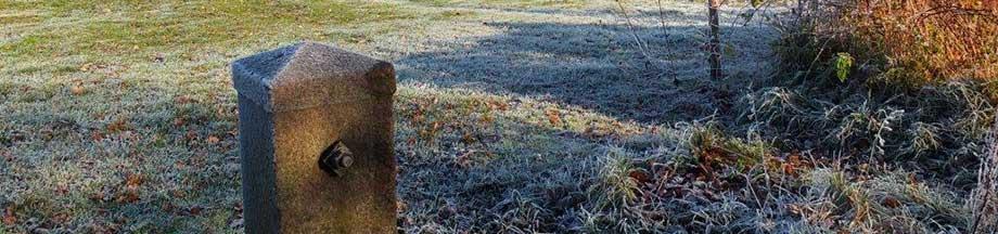 Einfaches Soldatengrab auf winterlichem Friedhof an der Ornumer Mühle